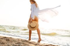 Cropped image of a attractive young woman. In summer clothes holding hat, walking along the beach Royalty Free Stock Photography