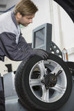 Cropped image of automobile mechanic repairing car's wheel in workshop Royalty Free Stock Photos