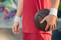 cropped image of basketball player in red sportswear holding basketball ball royalty free stock image