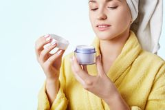 Cropped image of beautiful female wears gown and towel, has clear skin, holds jar with cosmetic cream, going to make mask, takes c. Are of her skin, over white royalty free stock image