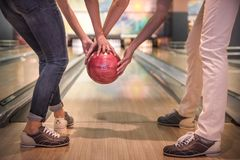Couple playing bowling. Cropped image of beautiful girl and handsome guy holding a bowling ball while playing stock photo