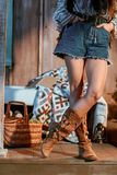 Cropped image of bohemian woman. In brown shoes and jeans shorts in a wooden house royalty free stock photo