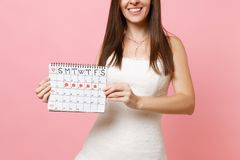 Cropped image of bride woman in white wedding dress holding female periods calendar for checking menstruation days. On pink background. Medical, healthcare royalty free stock photo