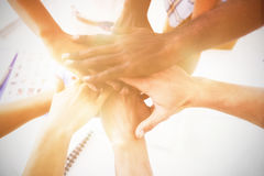 Cropped image of business colleagues stacking hands. At table in office royalty free stock photos