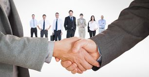 Cropped image of business people doing handshake with employees in background royalty free stock photos