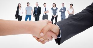 Cropped image of business people doing handshake with employees in background royalty free stock image