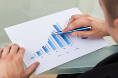 Cropped image of businessman analyzing bar chart with pen Royalty Free Stock Image