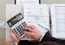 Cropped image of businessman calculating invoice at desk Royalty Free Stock Image