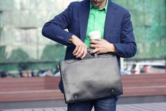 Cropped image businessman in casual wear with cup of coffee to go puts smartphone into trendy leather briefcase against modern stock photography