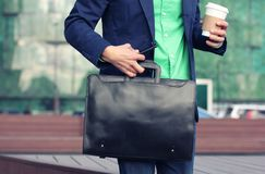 Cropped image businessman in casual wear tries to hold up cup of coffee to go, leather briefcase and smartphone at the same time. Against modern office building stock photo
