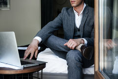 Cropped image of a businessman sitting on a bed Royalty Free Stock Image