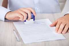 Cropped image of businessman stamping contract paper Royalty Free Stock Photo