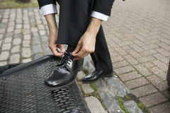 Cropped image of businessman tying his shoe on bench Royalty Free Stock Photo