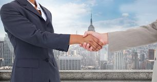Cropped image of businessmen doing handshake against city stock images