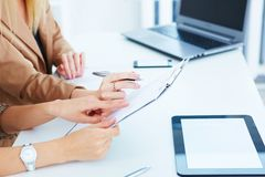 Cropped image of a businesswoman holding a pen and pointing at something at the clipboard while dealing with her colleague Royalty Free Stock Image