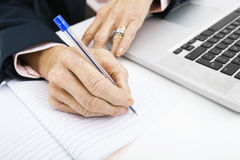 Cropped image of businesswoman with laptop writing in book on office desk Stock Photos