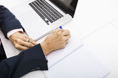 Cropped image of businesswoman with laptop writing in notebook on office desk Stock Photography