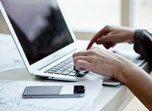 Cropped image of businesswoman with laptop writing in notebook on office desk. Stock Image