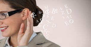 Cropped image of businesswoman listening alphabets. Digital composite of Cropped image of businesswoman listening alphabets Royalty Free Stock Photography