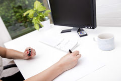 Cropped image of businesswoman noting on paper at computer desk Stock Photography