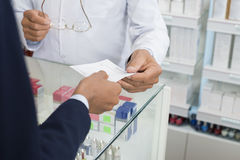 Cropped Image Of Businesswoman Showing Prescription To Chemist Stock Image