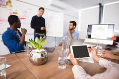 Cropped image of businesswoman using digital tablet while colleagues discussing in meeting room Royalty Free Stock Image