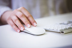 Cropped image of businesswoman using mouse on desk at office Royalty Free Stock Image