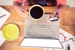 Cropped image of businesswoman using phone while holding coffee cup Royalty Free Stock Images