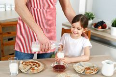 Cropped image of careful father wears apron, pours fresh milk in glass for his daughter, bakes delicious pancakes stock photography
