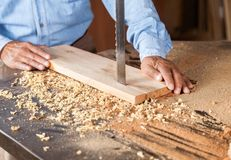 Cropped Image Of Carpenter Cutting Wood With Stock Photography