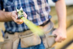 Cropped Image Of Carpenter Holding Tape Measure. Cropped image of manual worker holding tape measure outdoors Stock Photography