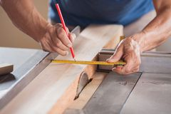 Cropped Image Of Carpenter Measuring Wood At Stock Image