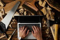 cropped image of carpenter typing on laptop surrounded by different tools on table royalty free stock photos