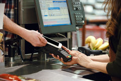 Cropped image of cashier woman create payment with phone app. Cropped image of cashier woman on workspace in supermarket shop create payment with mobile phone Stock Image
