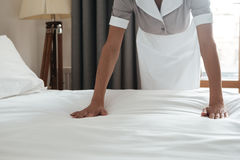 Cropped image of a chambermaid making bed in hotel room. Cropped image of a female young maid making bed in hotel room Stock Photography