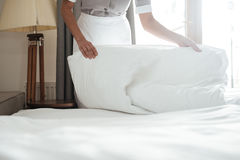 Cropped image of a chambermaid making bed in hotel room. Cropped image of a female young maid making bed in hotel room Royalty Free Stock Photography