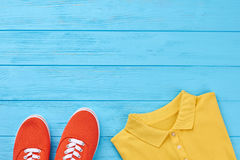 Cropped image of colored clothing. Shoes, t-shirt, blue wooden surface Stock Photography