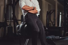 Cropped image of a confident businessman in formal clothes came to a gym for training after a hard day`s work. Stock Image