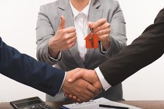 Cropped image of costumer and estate agent shaking hands, realty buying concept. Isolated on white stock photography