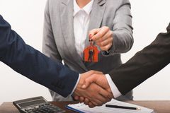 Cropped image of costumer and estate agent shaking hands, realty buying concept. Isolated on white stock photo