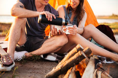 Cropped image of a couple drinking tea at the bonfire Royalty Free Stock Photography