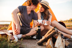 Cropped image of a couple drinking tea at the bonfire Stock Photos