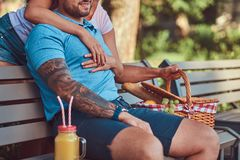 Cropped image of a couple wearing casual clothes during dating, having a picnic outdoors on a bench in the park. Cropped image of a couple wearing casual Royalty Free Stock Images