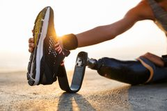 Cropped image of disabled athlete woman. With prosthetic leg doing stretching exercises outdoor at the beach royalty free stock images