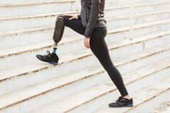 Cropped image of disabled running girl with prosthetic leg in sp. Ortswear working out at the stairs outdoors stock photos