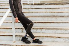 Cropped image of disabled sportswoman with prosthetic leg in tracksuit, standing at the stairs outside. Cropped image of disabled sportswoman with prosthetic leg royalty free stock images