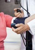 Cropped Image Of Doctor Checking Blood Pressure Of Senior Patien. Cropped image of mature male doctor checking blood pressure of senior women in rehab center Royalty Free Stock Image