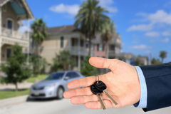 Cropped image of estate agent giving house keys  near with a vil Royalty Free Stock Photo