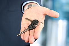 Cropped image of estate agent giving house keys. In office Stock Photos