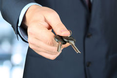 Cropped image of estate agent giving house keys in office. The Cropped image of estate agent giving house keys in office Royalty Free Stock Photography